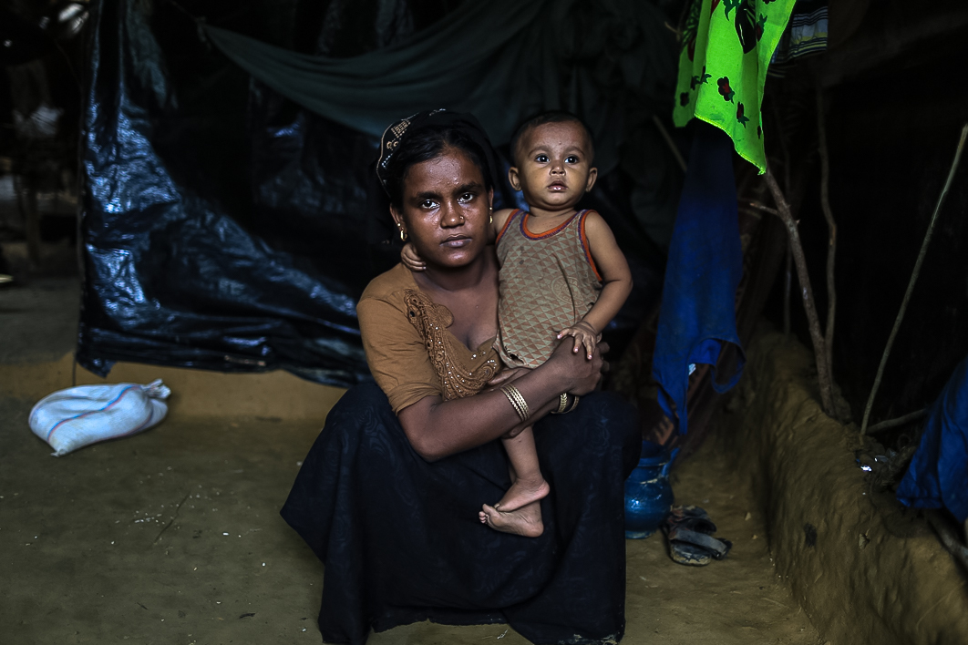 "Khalida, 20, with her one-year-old daughter Shahana. ""It took us five days to reach here and I consider myself fortunate that my entire family is with me,"" she says. ""The army had invaded our village and was burning houses and killing people. We also ran to save our lives and crossed over to Bangladesh on a boat. My husband goes out in the day to get relief material and food for us. I would want to go with him and get more food, but it's tough to stand in a queue with an infant and struggle to find food."" [Showkat Shafi/Al Jazeera]"