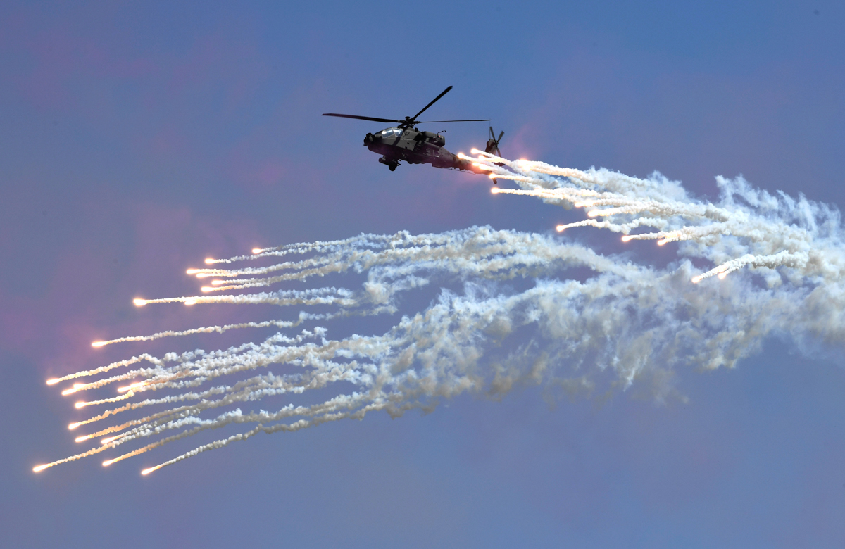 A South Korean Navy Lynx helicopter fires flares during a commemoration ceremony marking South Korea's Armed Forces Day [Jung Yeon-je/Pool/AP Photo]