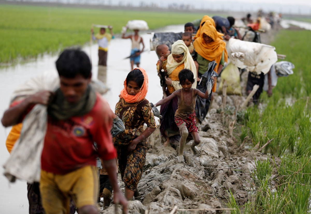 Rohingya refugees walk on the muddy path after crossing the Bangladesh-Myanmar border in Teknaf, Bangladesh. [Mohammad Ponir Hossain/Reuters]