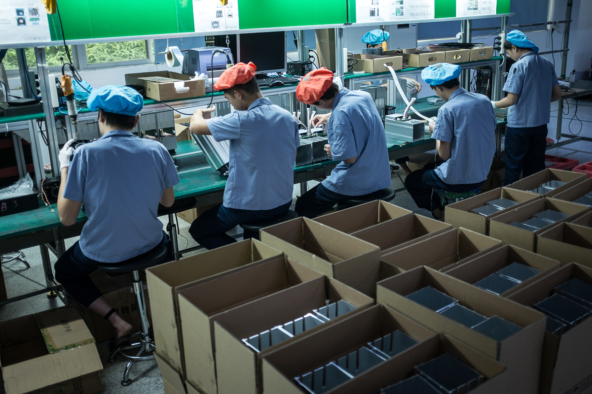 Employees work on an assembly line of AntMiner S9 mining machines at Bitmain's manufacturing base, Shenzhen, China. [EPA/Liu Xingzhe/CHINAFILE]