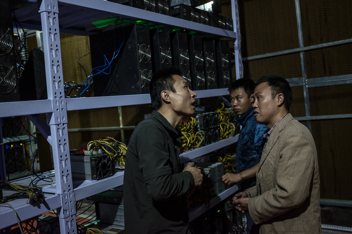 Bitcoin miner Liu, left, meets with clients. He moved from Henan province to Sichuan province in 2015 for cheaper electricity. Now, he manages more than 7,000 mining machines. Meanwhile, his clients can monitor the machines' operation and bitcoin earnings remotely using apps and mobile phones. [EPA/Liu Xingzhe/CHINAFILE]