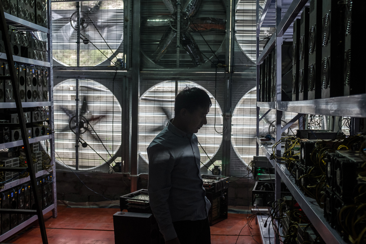 Bitcoin mine owner Liu, 29, stands in front of a wall of cooling fans at his mine where he houses and operates mining machines for those who do not want to move to rural Sichuan. [EPA/Liu Xingzhe/CHINAFILE]