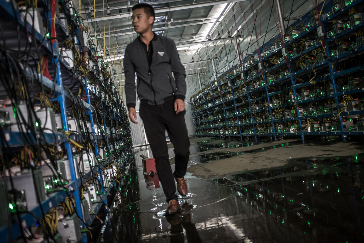 Tibetan bitcoin mine manager Kun walks between aisles of mining machines. Kun is the mine's manager as well as one of its investors. He learned about bitcoin through a friend and started investing in 2015. [EPA/Liu Xingzhe/CHINAFILE]
