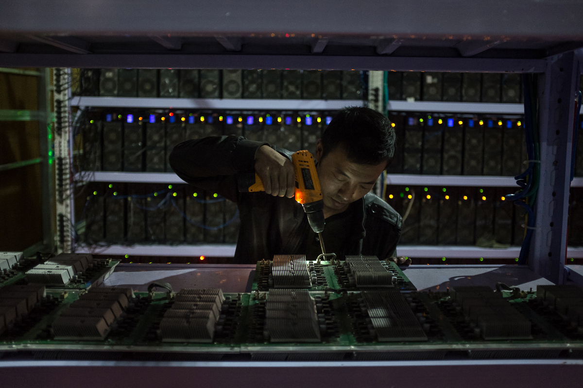 An employee assembles a calculation board at a bitcoin mine in Sichuan Province, China. Sichuan has become known as the capital of bitcoin mining; with an abundance of hydropower, it can cope with the electricity needs. [EPA/Liu Xingzhe/CHINAFILE]
