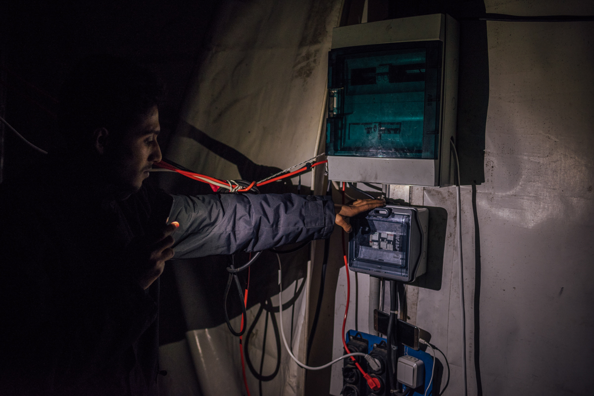 A Syrian refugee is showing the main electricity switch inside a larger tent, hosting hundreds of people. 'There is no electricity here for weeks and in here it is often colder than outside,' he said. [Kevin McElvaney/Al Jazeera]