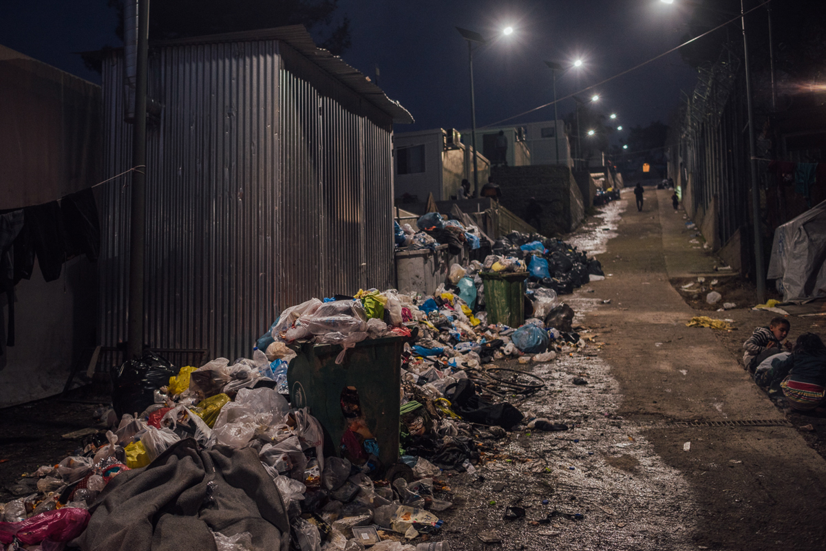 Piles of waste are spread all over the camp. Residents accuse authorities of not cleaning the designated areas every week. It is estimated that Moria camp is hosting more than 2.5 times more people than its intended capacity. [Kevin McElvaney/Al Jazeera]