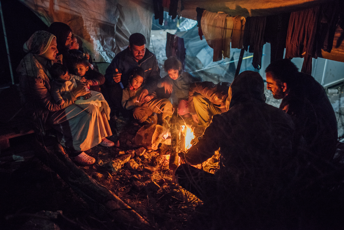 Syrian and Iraqi asylum seekers share a fireplace between their tents. For many Moria camp residents, this is the only way to protect themselves from the plummeting winter temperatures. [Kevin McElvaney/Al Jazeera]