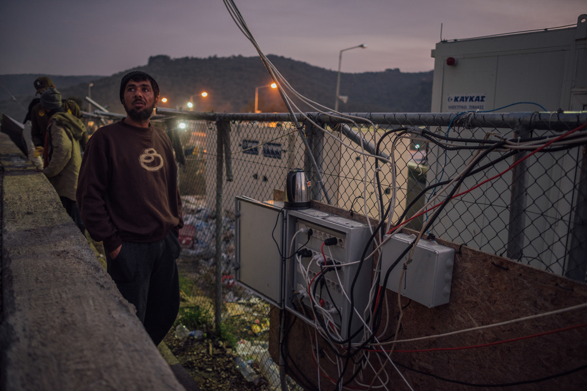 An asylum seeker is making tea at one of the camp's rare functioning electricity spots. The network often collapses and people do not have access to power for days. [Kevin McElvaney/Al Jazeera]