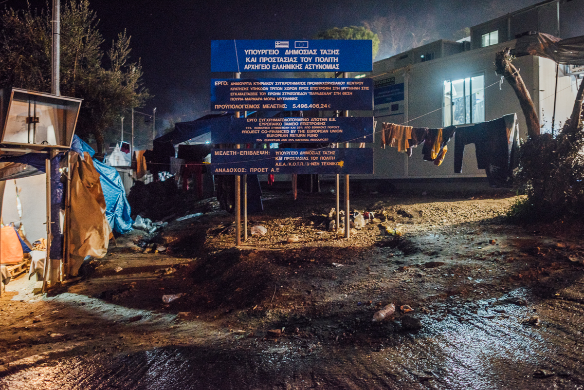 A sign reads that the EU and the Greek government spent more than 5.4 million euro ($6.6m) on Moria camp. [Kevin McElvaney/Al Jazeera]