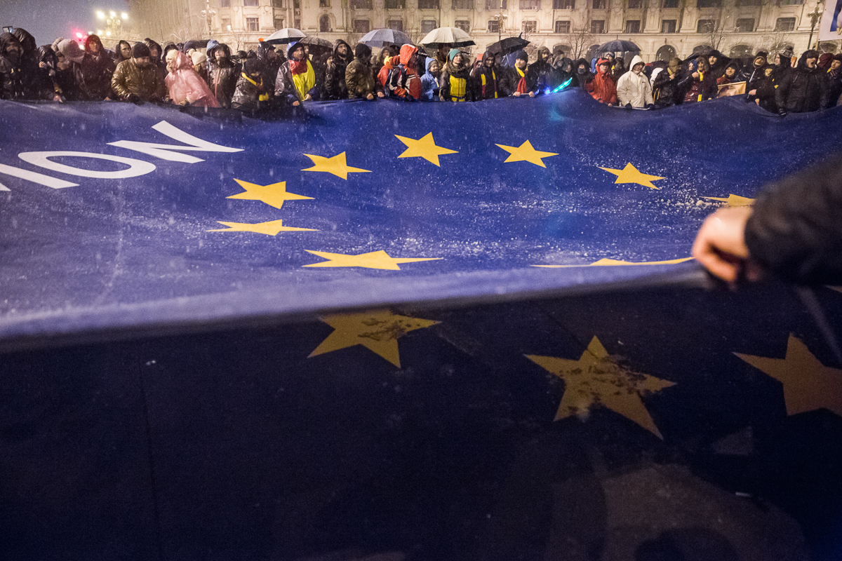 Demonstrators hold a giant European Union flag during the protest in front of the Romanian Parliament building in Bucharest. [Ioana Moldovan/Al Jazeera]