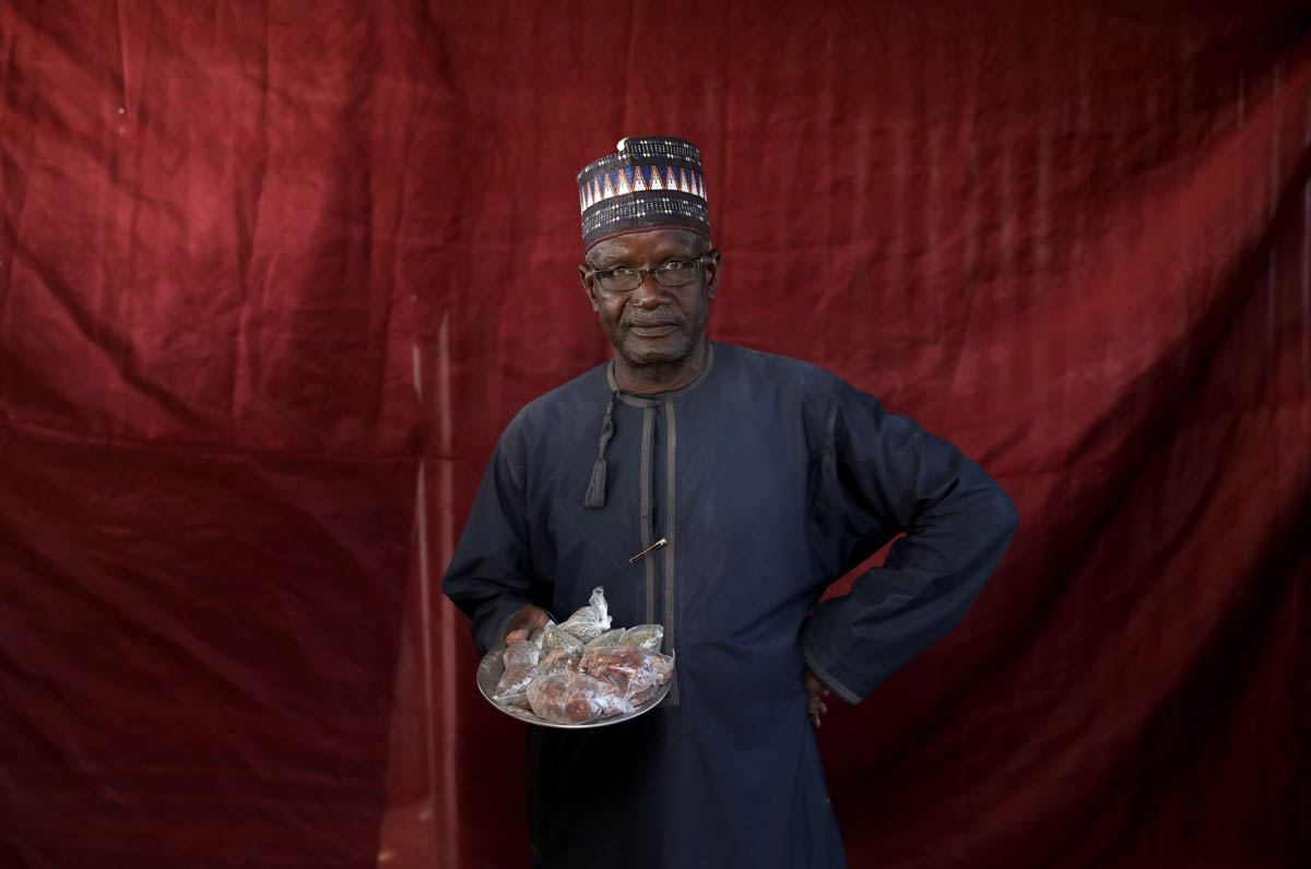 Jibril Adamu holds okra seeds and sugared groundnuts, ready for exchange. [Afolabi Sotunde/Reuters]