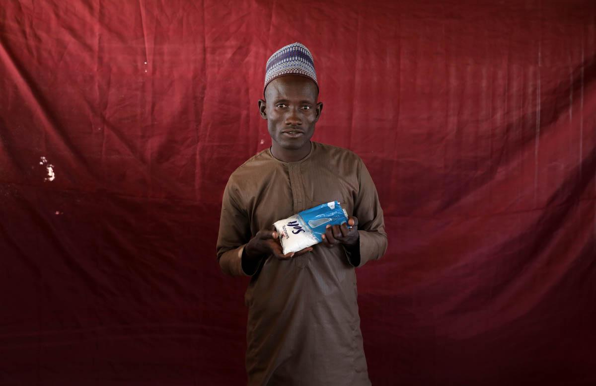 Insua Damladi holds up a sachet of salt. [Afolabi Sotunde/Reuters]