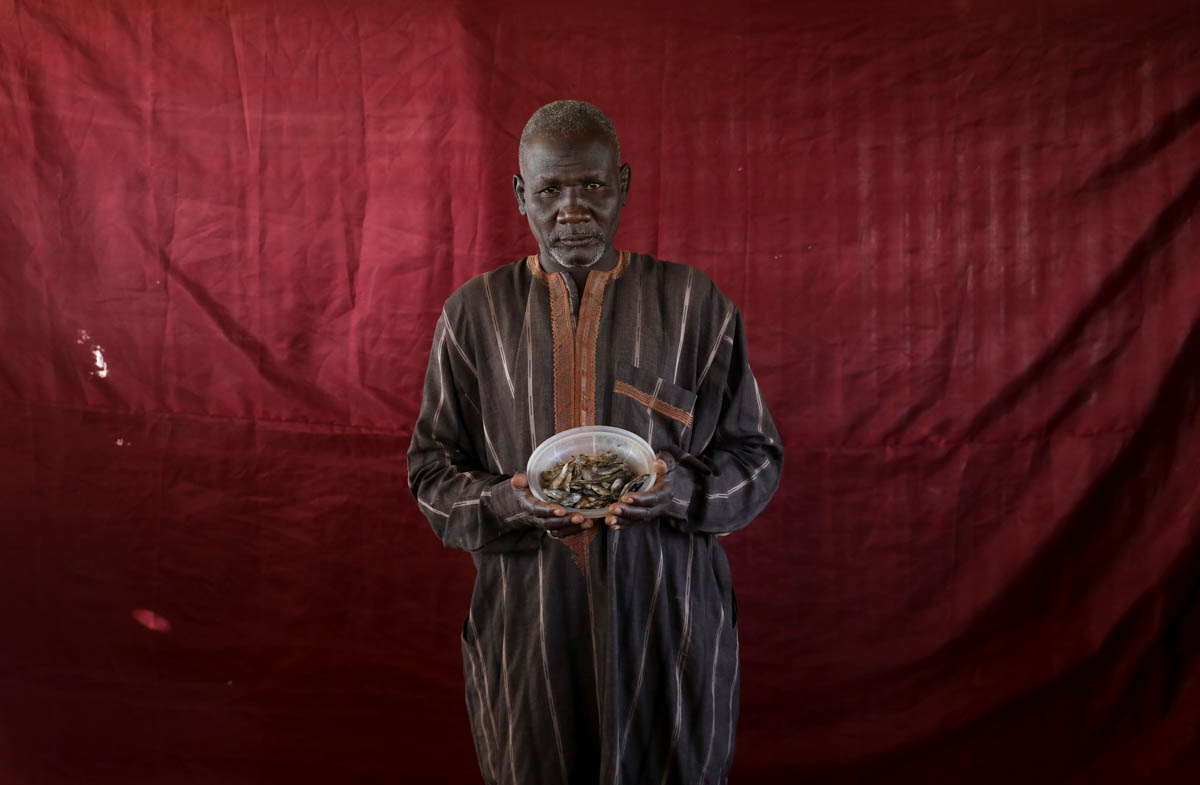 Abdulwahal Abdulla, a 50-year-old living in Bakasi for three years, hoped to trade this bowl of dried young tilapia fish worth roughly 150 naira for cooking oil. Abdulla, no fan of the fish, had bought them because products were scarce and it was the only thing he could buy at the time, he said. [Afolabi Sotunde/Reuters]