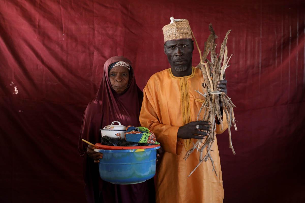Aisha Umaru (L) holds a basin of milk as Umaru Usman Kaski holds firewood at the Bakasi IDP camp, Maiduguri, Nigeria. [Afolabi Sotunde/Reuters]
