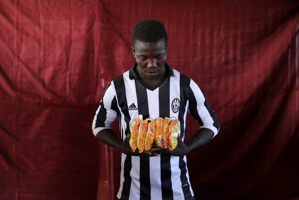 Abachi Mohammed holds six packets of chicken-flavoured instant noodles. [Afolabi Sotunde/Reuters]