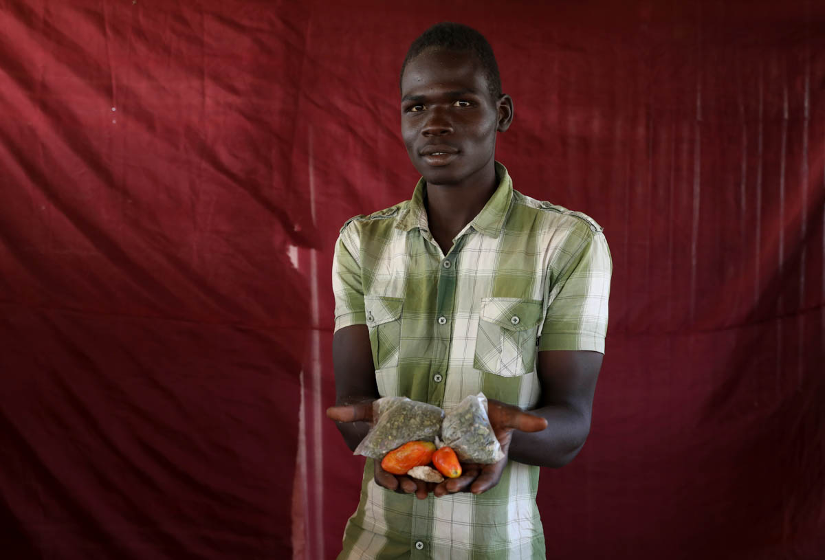 Mohammed Ali holds up two tomatoes and some dried vegetable leaves. [Afolabi Sotunde/Reuters]