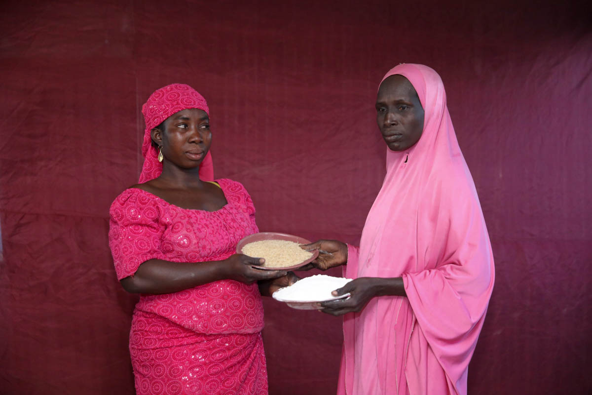 Falmata Madu exchanges her plate of uncooked rice for Hadisa Adamu's ground maize. Many of those responding to the crisis are also concerned that with economic prospects dim for the foreseeable future, millions of people will become dependent on aid, the vast majority of it coming from overseas. Until then, Nigeria's displaced are finding their own ways to balance what they receive with their needs. [Afolabi Sotunde/Reuters]