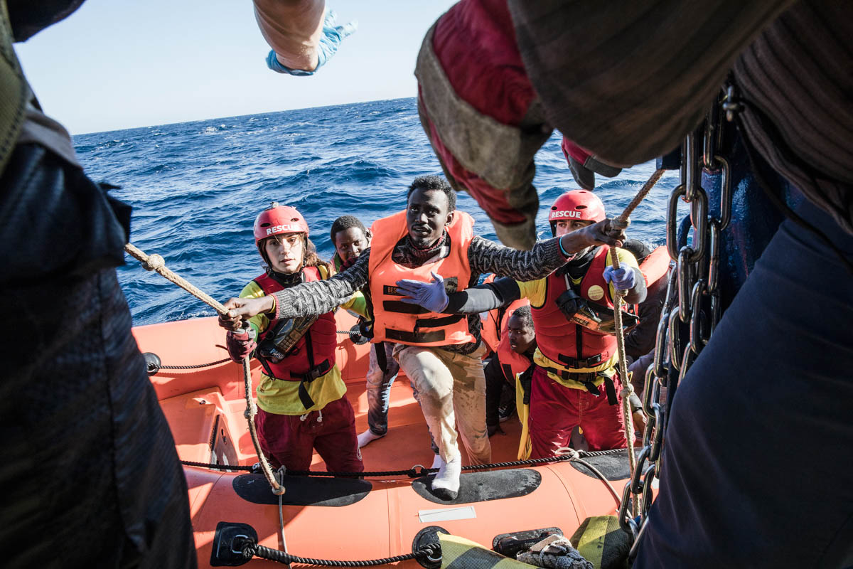 Refugees, mostly from Eritrea, are rescued from an overcrowded wooden boat, 34 miles north of Kasr El-Karabulli in Libya. [Giuseppe Carotenuto/Al Jazeera]
