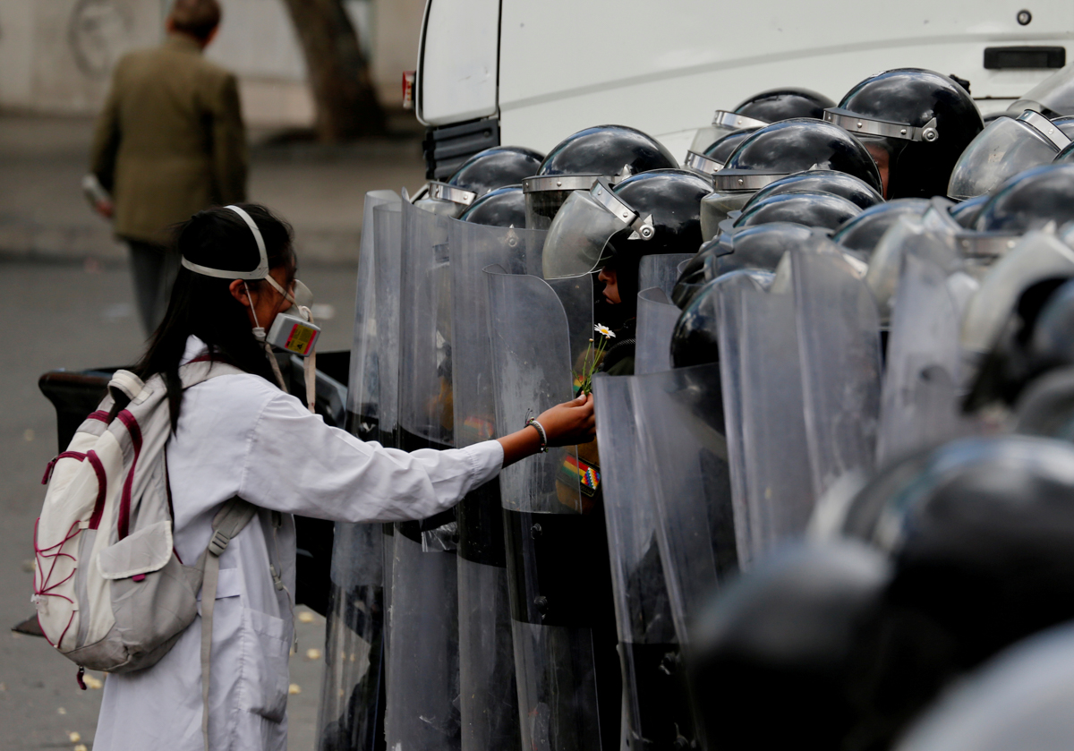 A demonstrator in La Paz gives a flower to a riot police officer during a rally against Bolivia's new healthcare policies. [David Mercado/Reuters]