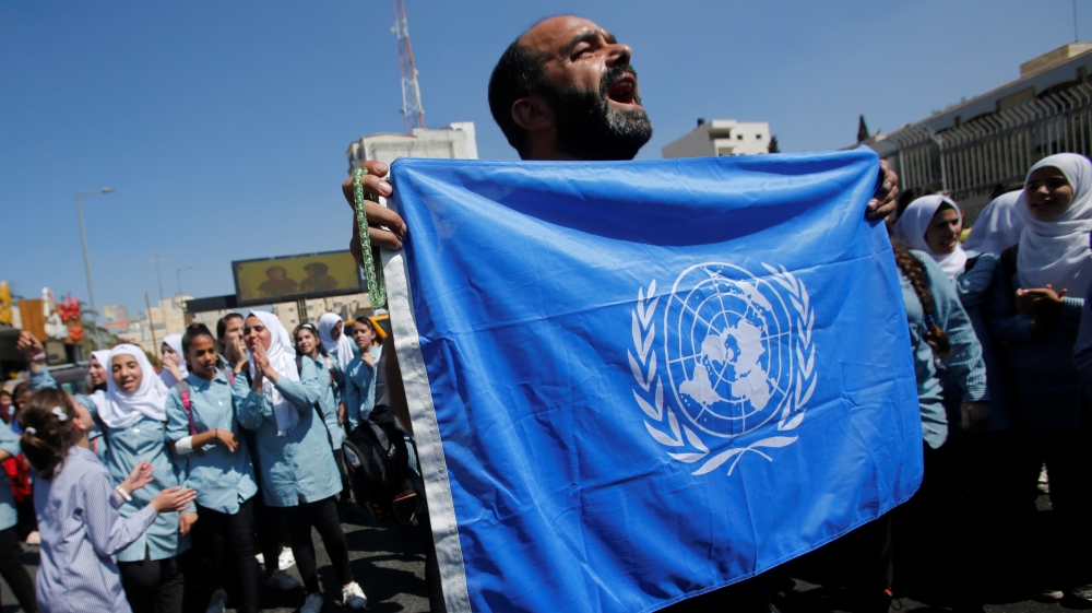 Palestinian demonstrator holds UN flag during a rally against a U.S. decision to cut funding to UNRWA and in support of president Mahmoud Abbas, in Bethlehem in the occupied West Bank