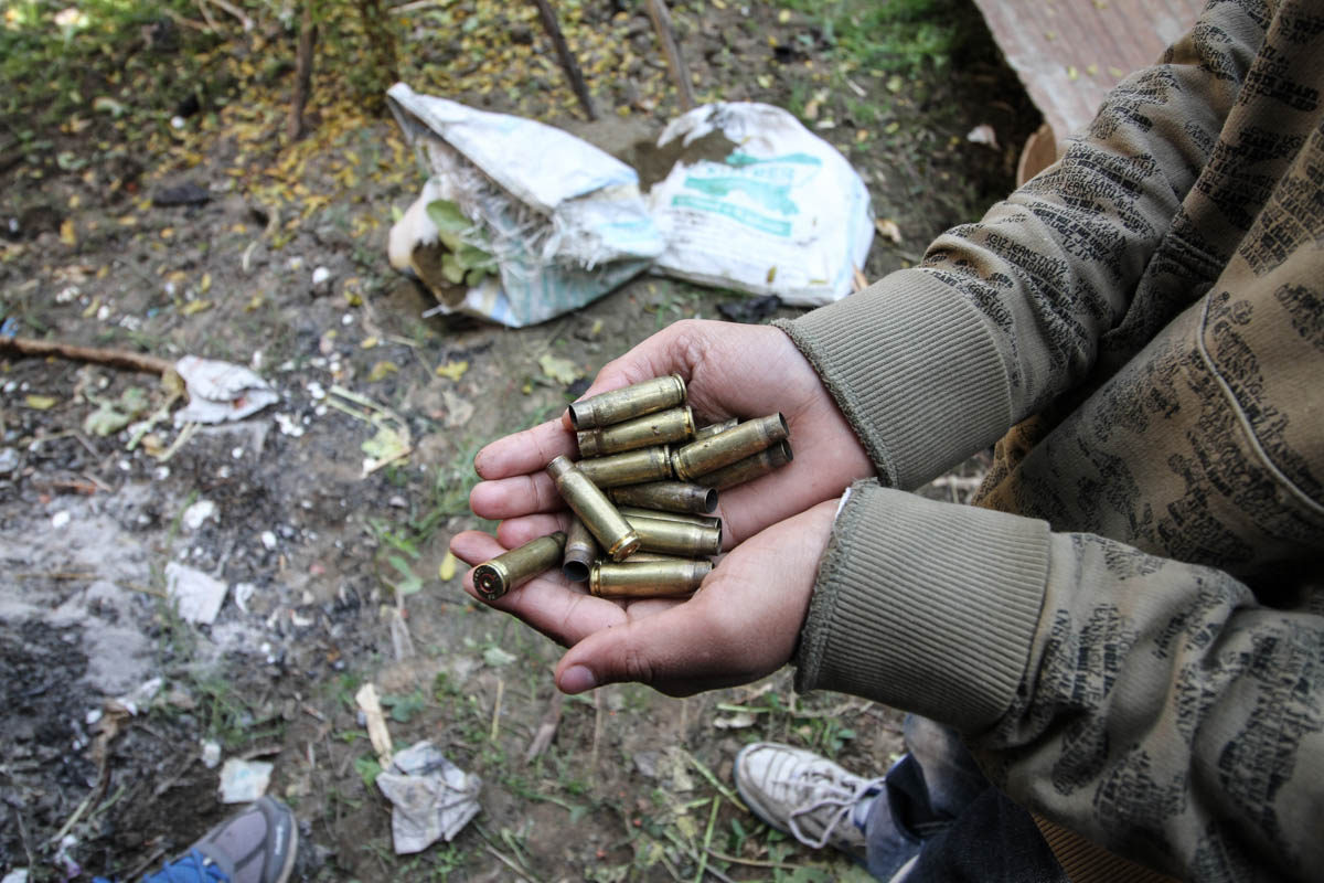 A boy gathers bullet shells following a gun battle. Experts have warned of grave effects of the decades-old conflict on Kashmir's children. [Sameer Mushtaq/Al Jazeera]