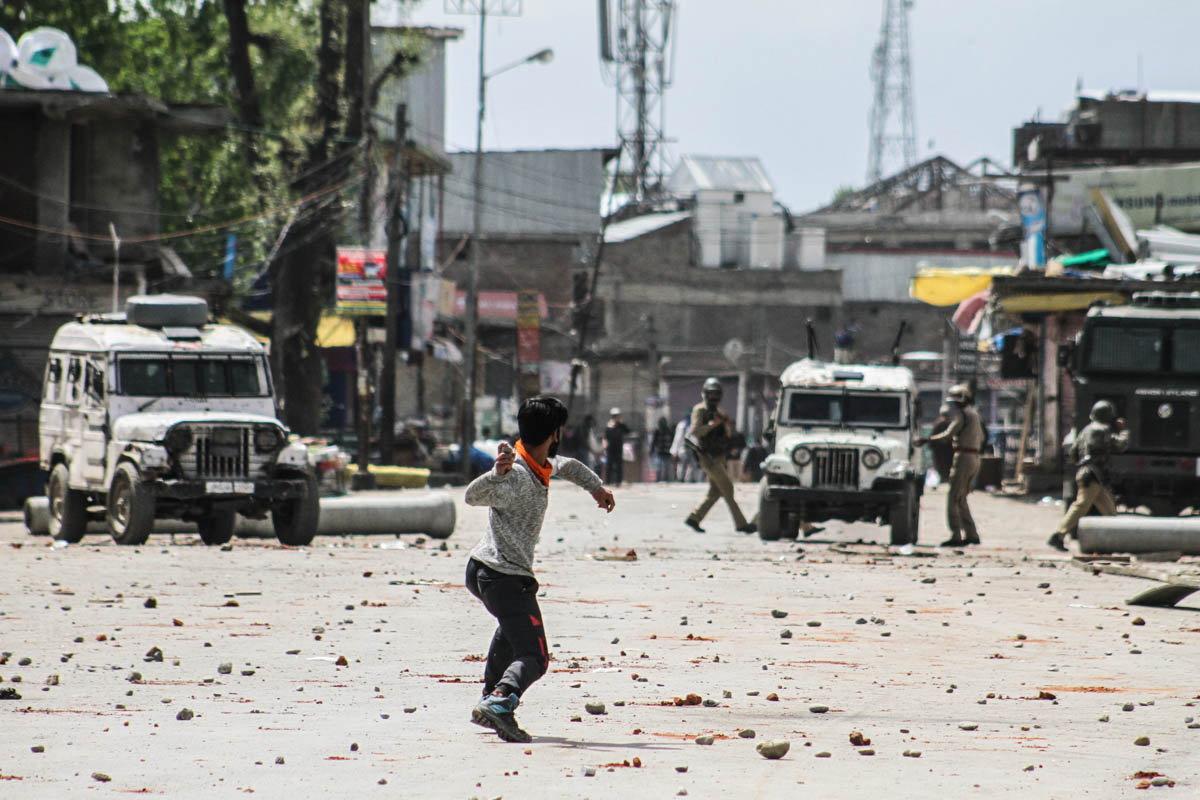 A Kashmiri protester throws stones at Indian police and paramilitary forces. Stone pelting has now become a norm in Kashmir as tear gas shells, pellets and sometimes even live bullets are used against the protesters. [Sameer Mushtaq/Al Jazeera]