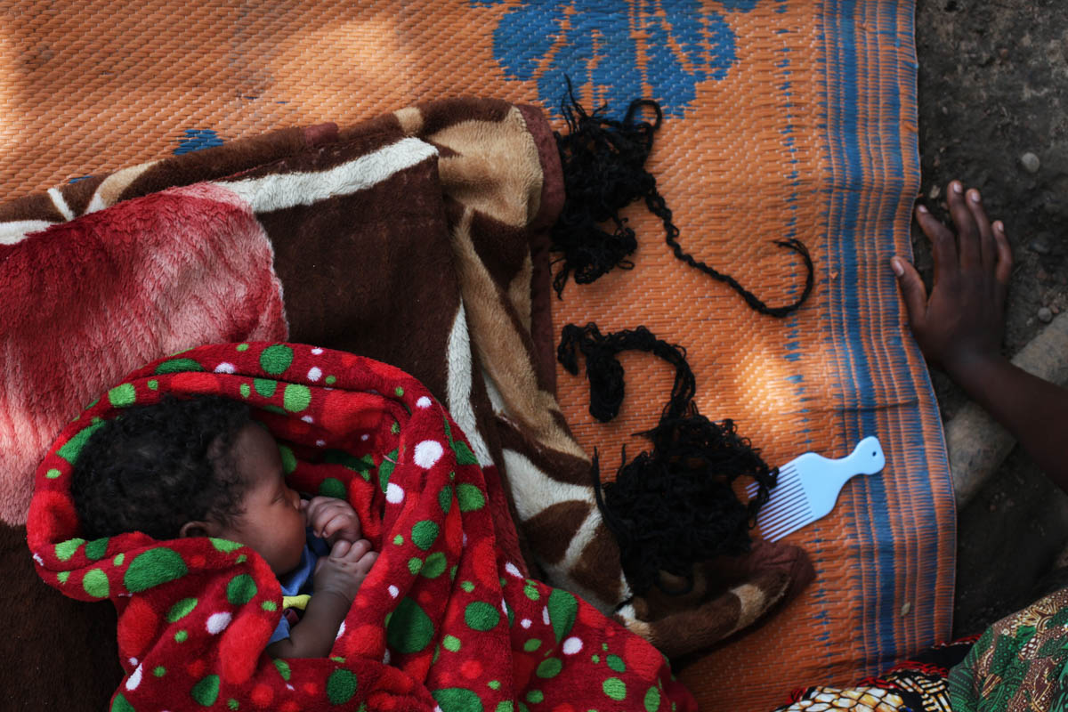 "The one-month-old baby girl of a mother, 16, who was held by rebel soldiers, is sleeping on a mat in their compound, outside Yambio. The mother was made a second wife for one of the soldiers, but other men were sleeping with her, too. She doesn't know who the father is, but she loves the child. ""My grand-mother welcomed me when I came back, and the child when she was born. But some neighbors were scared. They said I had the mindset of the people in the bush. I was made to kill and maybe I would do it again"". She's learning tailoring but after, would like to go back to primary school. She says till today, she doesn't dare to go back to the fields because she's scared of being abducted again. [Andreea Campeanu/Al Jazeera]"