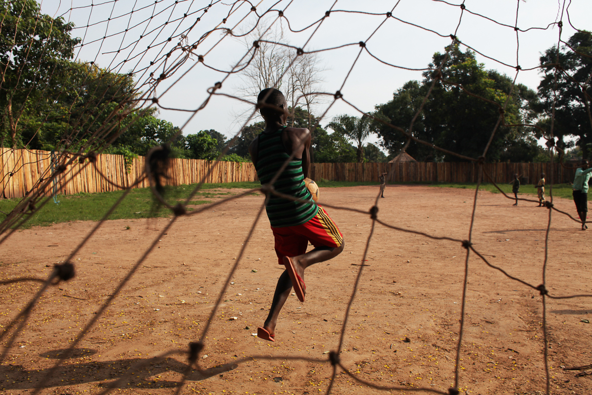 A 16-year-old boy who was a bodyguard in the opposition group South Sudan National Liberation Movement (SSNLM) plays football outside the transit center ran by World Vision and UNI. [Andreea Campeanu/Al Jazeera]