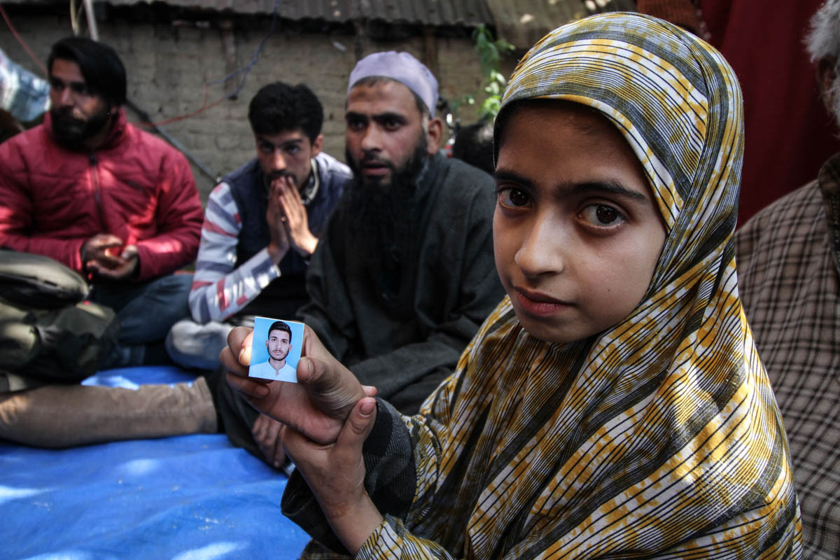 The sister of Mohammad Muqeem holding his photograph in Kulgam's Laroo village. Muqeem, a class 12 student, was one of the seven civilians killed on October 21. 'He had to appear in his board examination four days later. I never expected that he would meet this fate,' a relative of Muqeem said. [Sameer Mushtaq/Al Jazeera]