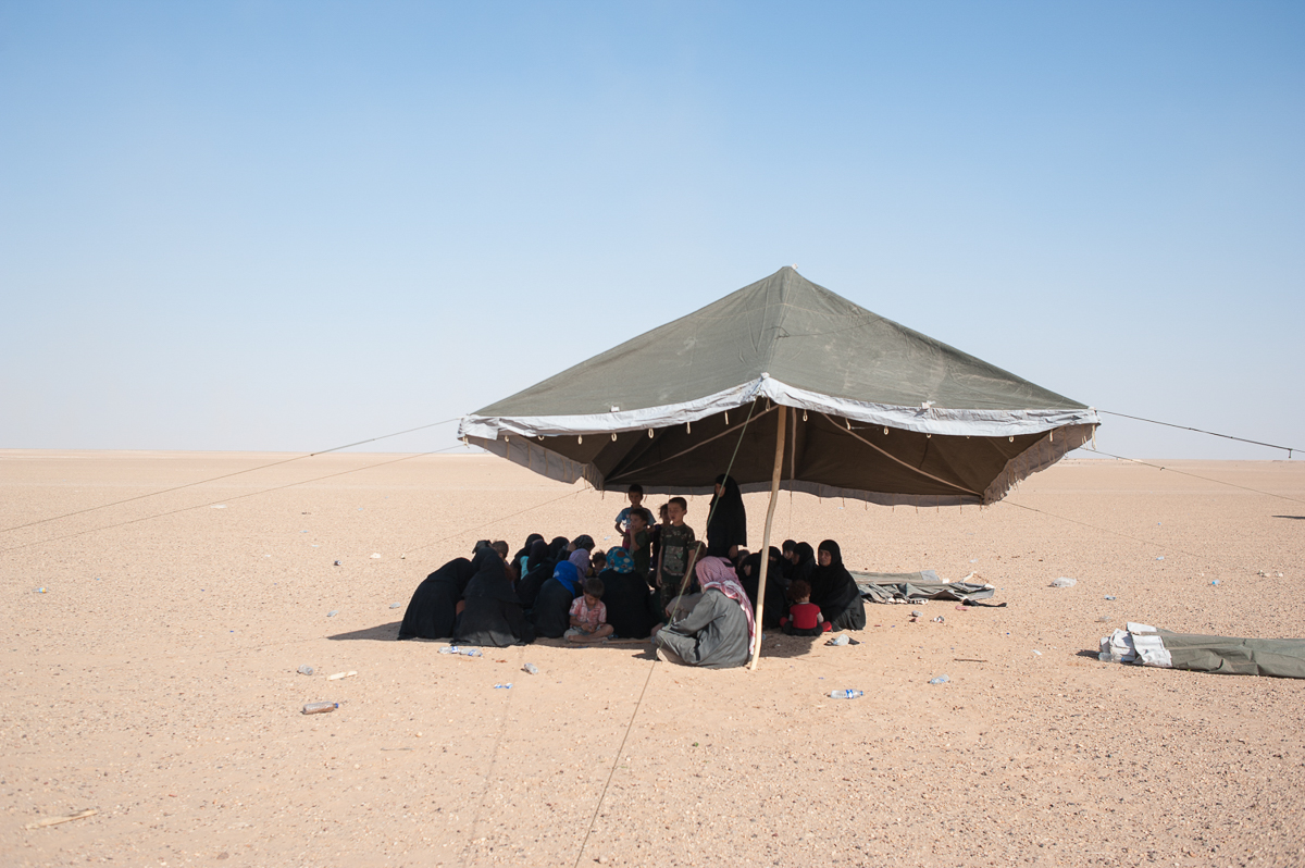 Under a tent in the desert people displaced  from Hajin wait to be identified by SDF intelligence forces and be allowed to enter a the temporary IDP camp. [Linda Dorigo/Al Jazeera]