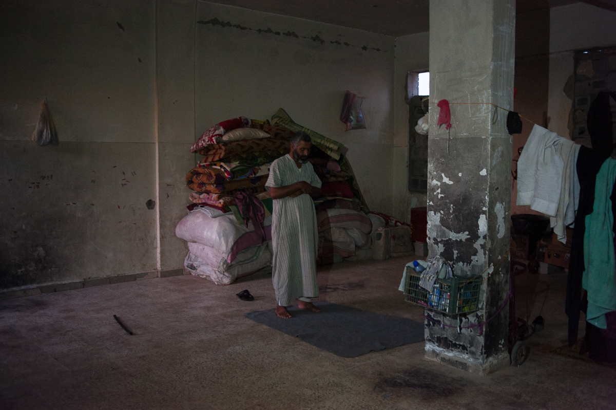 A man prays on the ground floor of the abandoned school of Harijieh, 80km north of Hajin; 100 people from Deir Az Zor found home in the empty rooms of the building [Linda Dorigo/Al Jazeera]