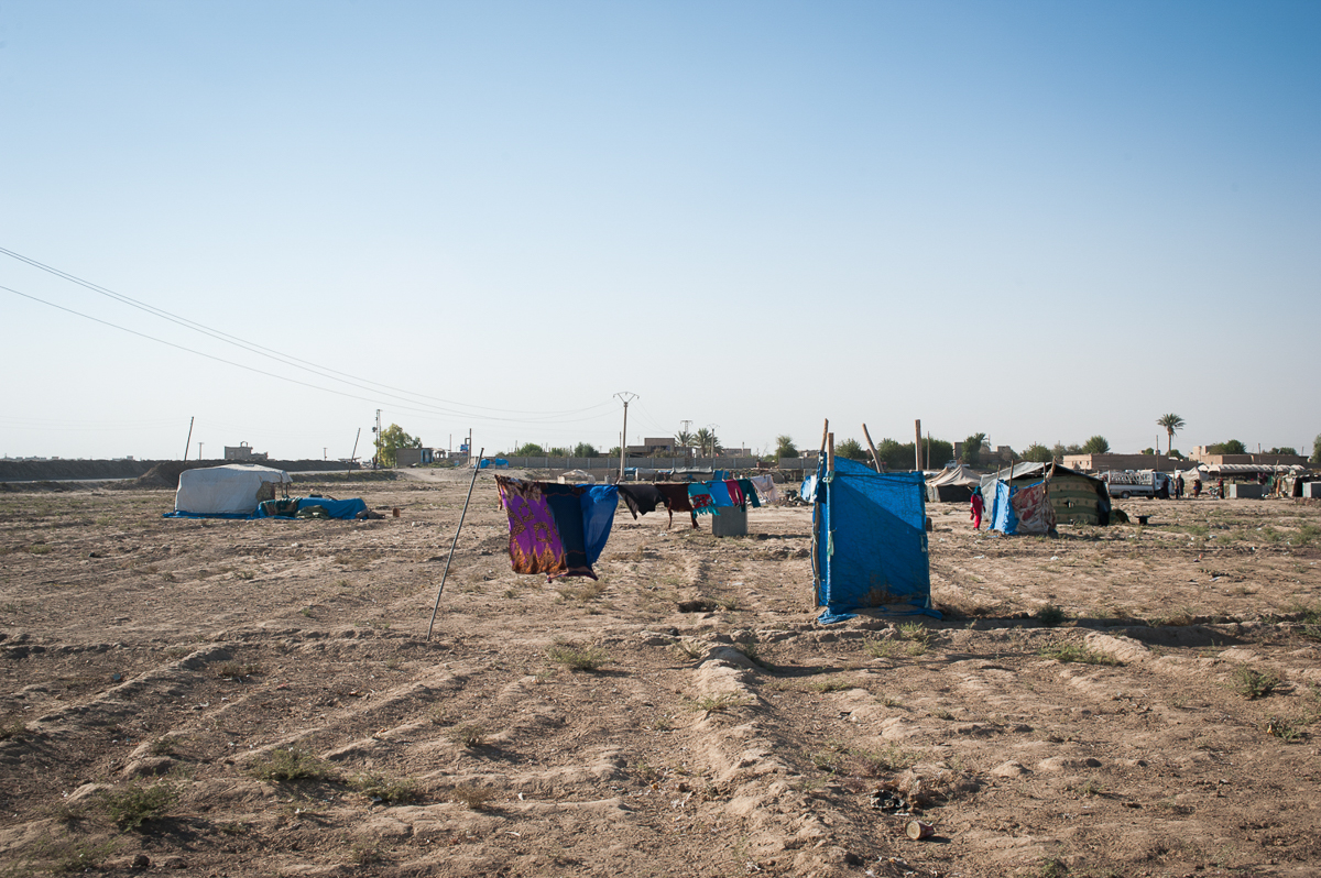 Two-hundred families live in the camp of Bahara in Deir ez-Zor, where hygienic conditions are very poor. The blue curtain (pictured) shields a communal toilet. [Linda Dorigo/Al Jazeera]
