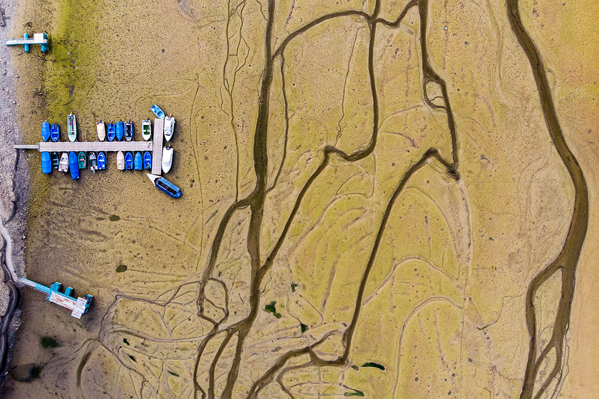 Stranded boats along the dried-out shores of the Brenet Lake along the border of France and Switzerland. [Anthony Anex/EPA]