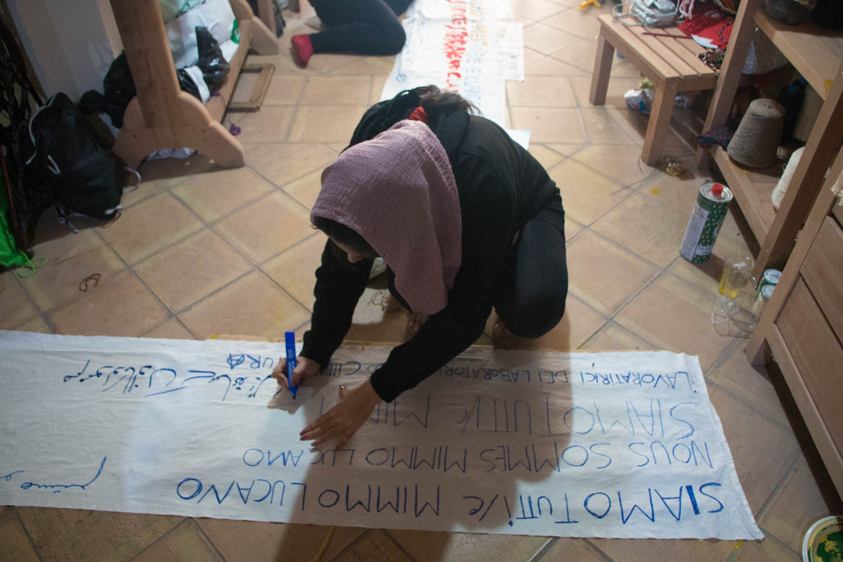 Morsal is 17 and from Afghanistan. She arrived via Turkey and the Mediterranean seven years ago and now goes to school and speaks perfect Italian. The banner she''s writing in preparation for the demonstration reads 'We are all Mimmo Lucano.' [Ylenia Gostoli/Al Jazeera]