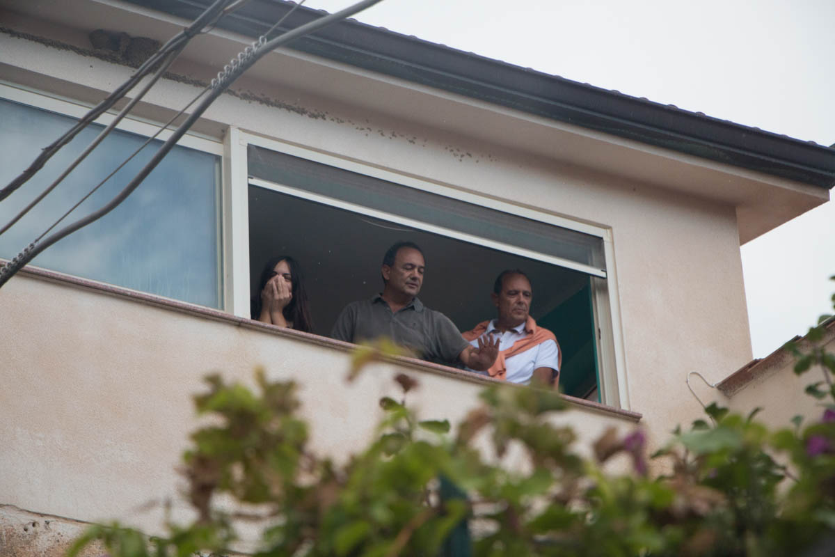Domenico Lucano, who is under house arrest, and his family and friends came to the window, moved by the crowd. 'It is to disregard these foolish laws that I go against the law,' Lucano says in the wiretapped phone conversation. [Ylenia Gostoli/Al Jazeera]
