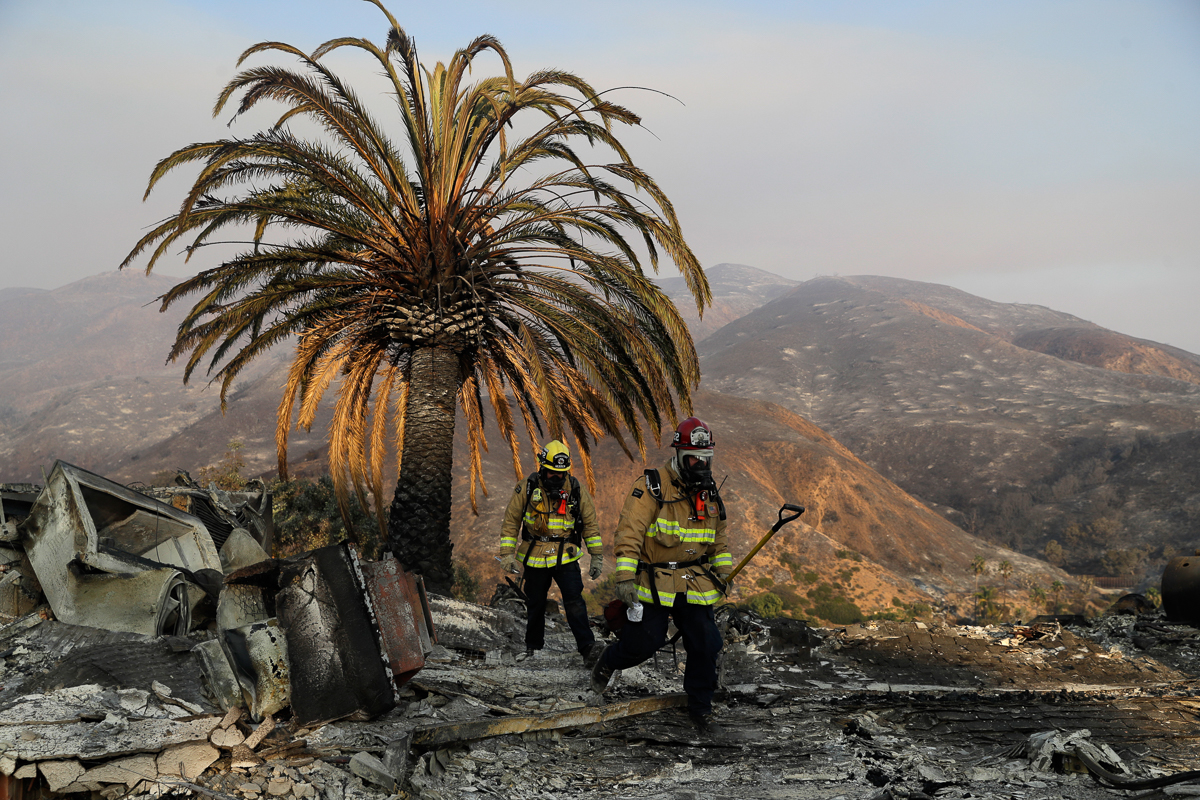 November - Fire fighters walk among the ashes of a wildfire-ravaged home in Malibu, California. The Camp Fire, in the northern part of the state, was the deadliest and most destructive wildfire in California's history, responsible for at least 86 deaths and the destruction of more than 18,000 structures. [Marcio Jose Sanchez/AP]