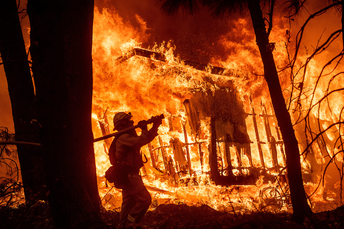 Firefighter Jose Corona fights the flames consuming a home in Magalia, California. [Noah Berger/AP Photo]