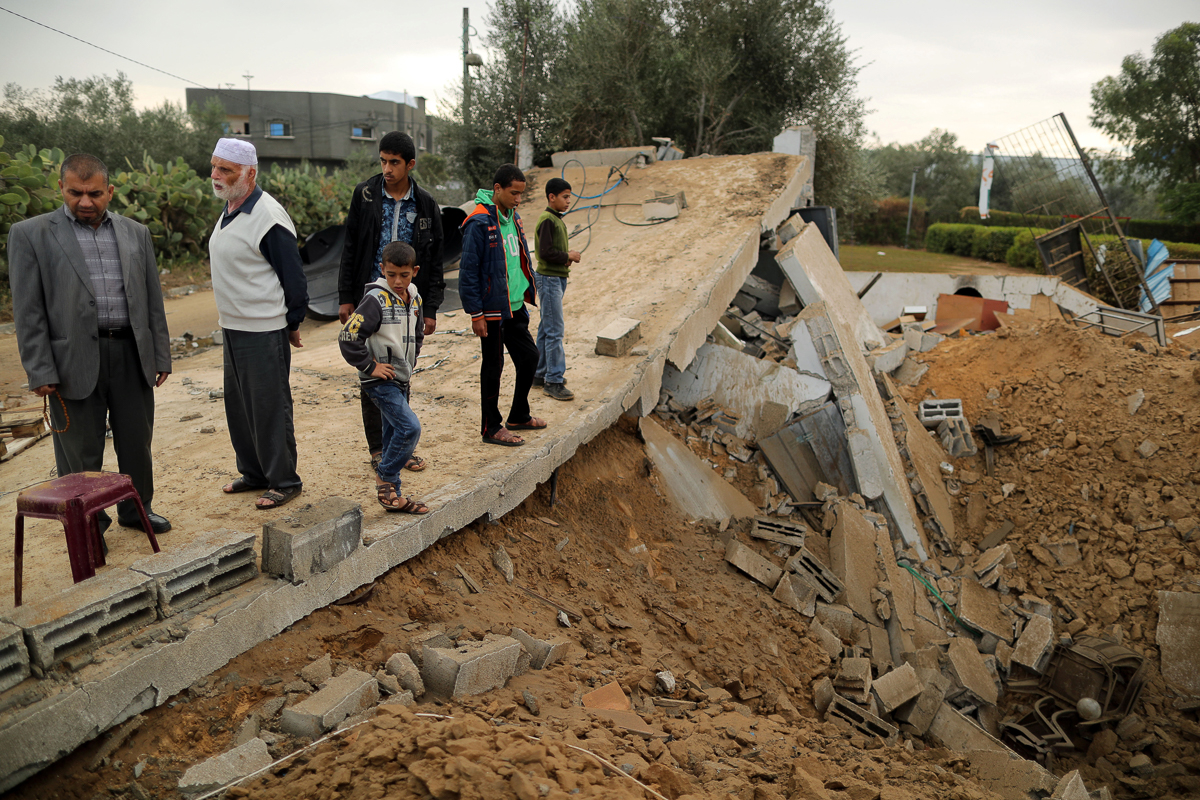 Palestinians stand on the ruins of a building  destroyed in an Israeli air attack in Khan Younis. [Suhaib Salem/Reuters]