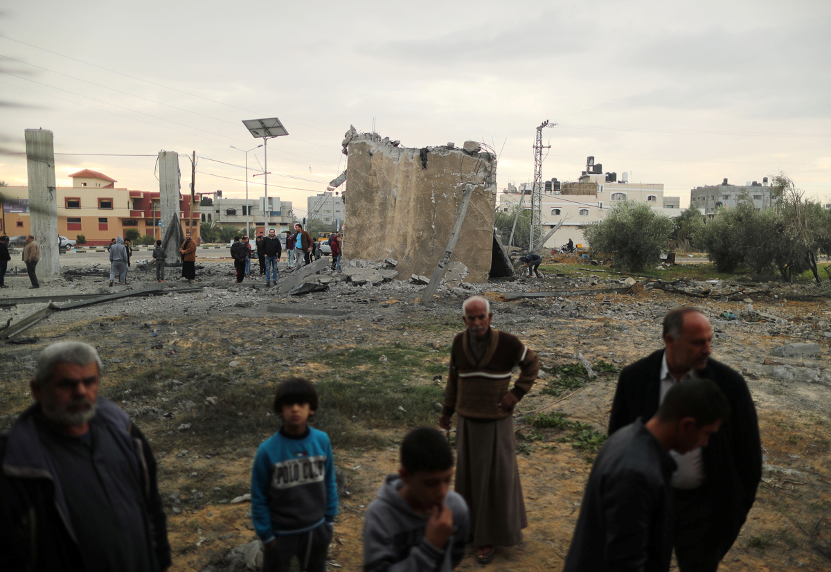Palestinians gather at the ruins of a building destroyed by an Israeli air attack in Khan Younis in the southern Gaza Strip. [Suhaib Salem/Reuters]