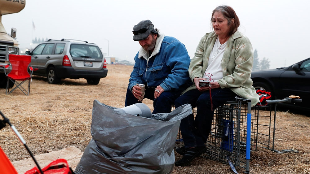 Anna and William Goodnight of Paradise sit outside their tent at a makeshift evacuation centre for people displaced