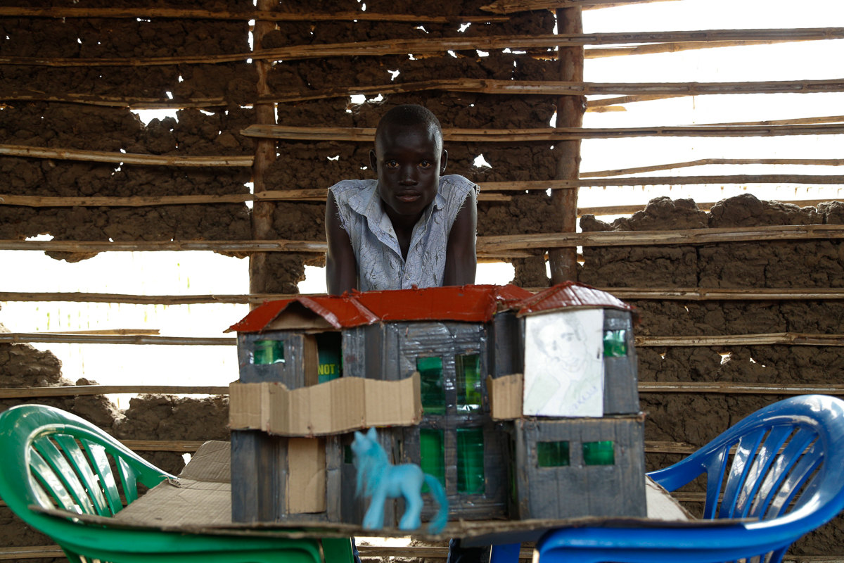 A teenage boy in the Gurei neighbourhood of Juba builds small houses completely out of scratch from materials like cardboard to sell and give away. [Viktorija Mickute/Al Jazeera]