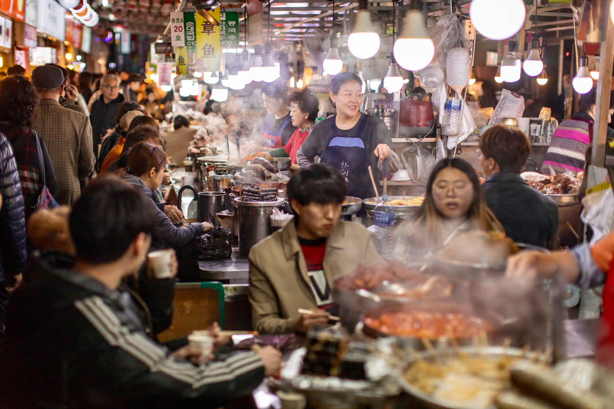 Steam, sounds and smells consume the tightly packed market streets along with hundreds of eager customers keen for cheap, traditional Korean cuisine. [Joel Lawrence/Al Jazeera]
