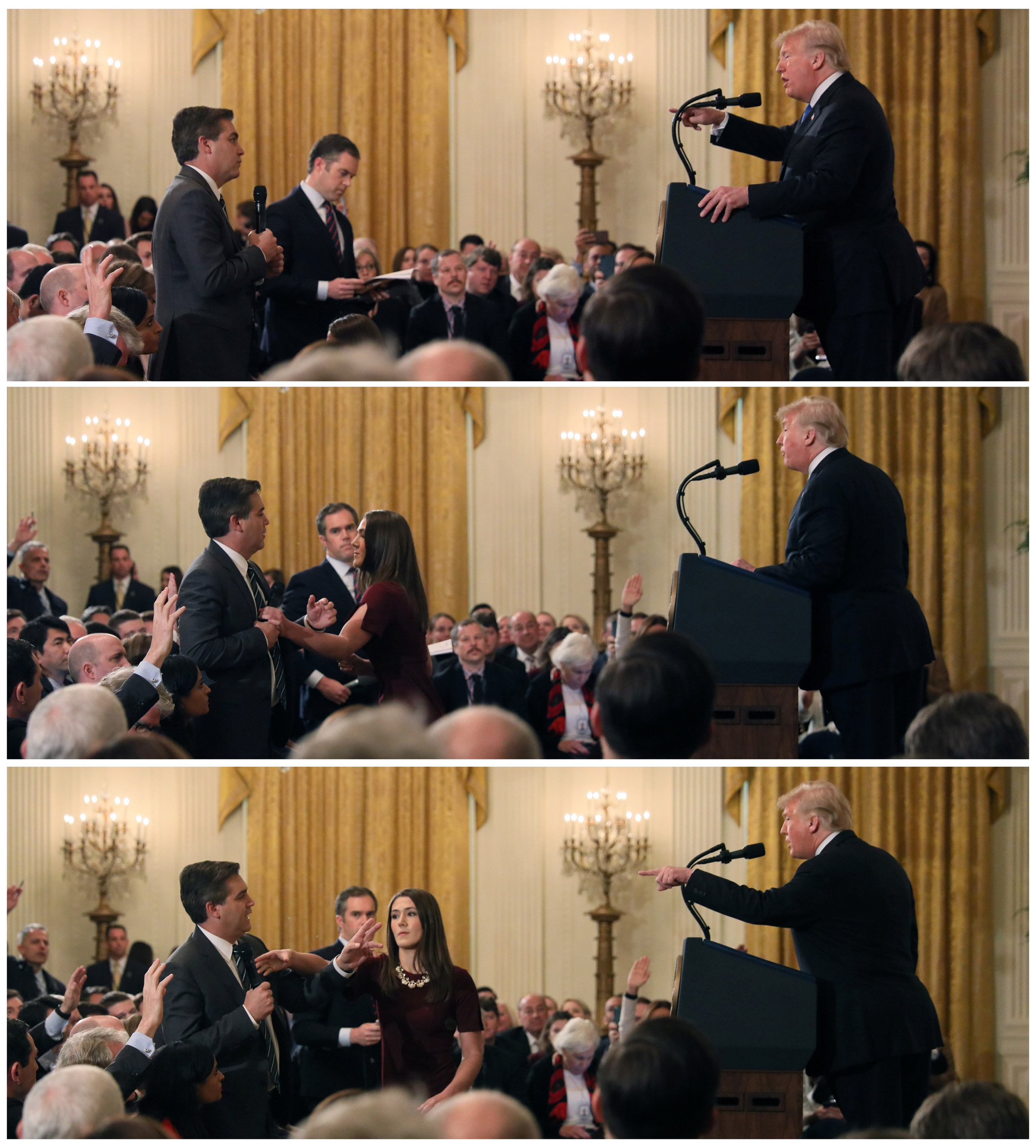 A White House staff member reaches for the microphone held by CNN's Jim Acosta as he questions US President Donald Trump