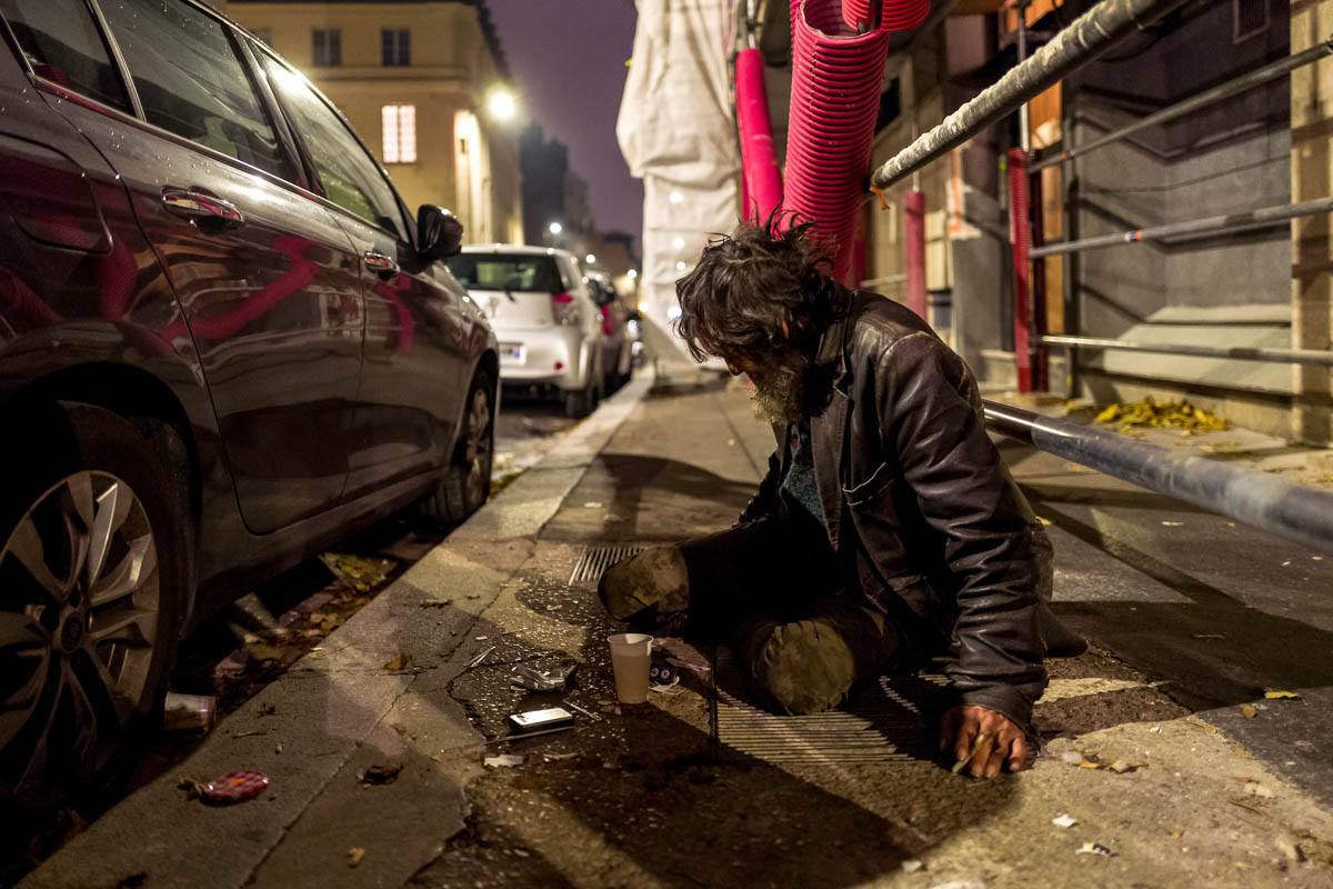 Dominic sits on a street in the centre of Paris. He has been homeless for the past 20 years. A medical patrol by a team of volunteers working with Medecins du Monde provide him with a hot drink and a conversation, something Dominic says he misses the most. [Omar Havana/Al Jazeera]