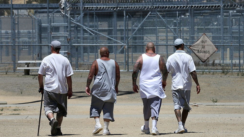 Inmates walk the exercise yard at the California Medical Facility in Vacaville California
