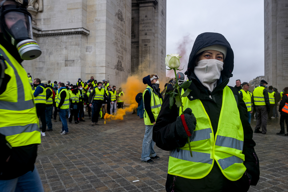 A protester holds a flower as a symbol of a peaceful protest under the world famous Arc de Triomphe. As a result of the violent protest, access to the Champs Elysees was blocked off by police barricades, forcing protesters to neighbouring streets. [Omar Havana/Al Jazeera]