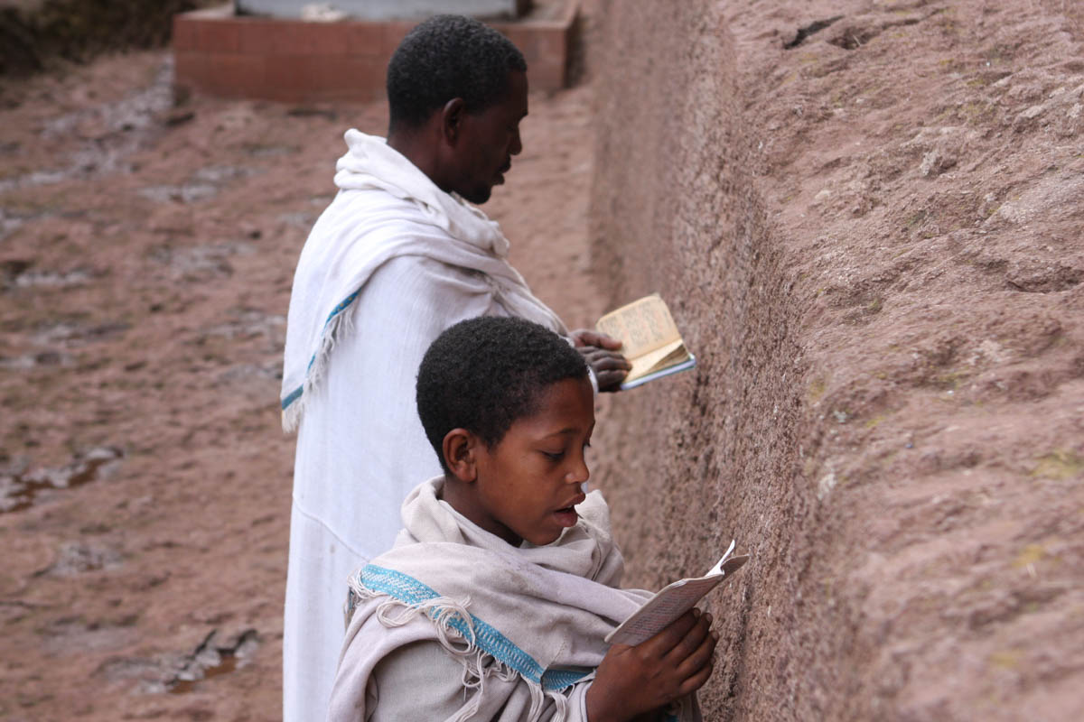 A man and young boy reciting prayers outside the walls of Bet Maryam, one of the larger churches dedicated to the Virgin Mary. Tradition has it that this was the first church excavated at Lalibela, and today it serves as a particularly poplar shrine with local pilgrims. 'These churches are a place to connect with heaven,' says Kidanemariam Woldegeorgis, an Ethiopian archeologist working with the Lalibela Mission. 'It's their Jerusalem. At Christmas people come from all over Ethiopia to worship here.' [James Jeffrey/Al Jazeera]