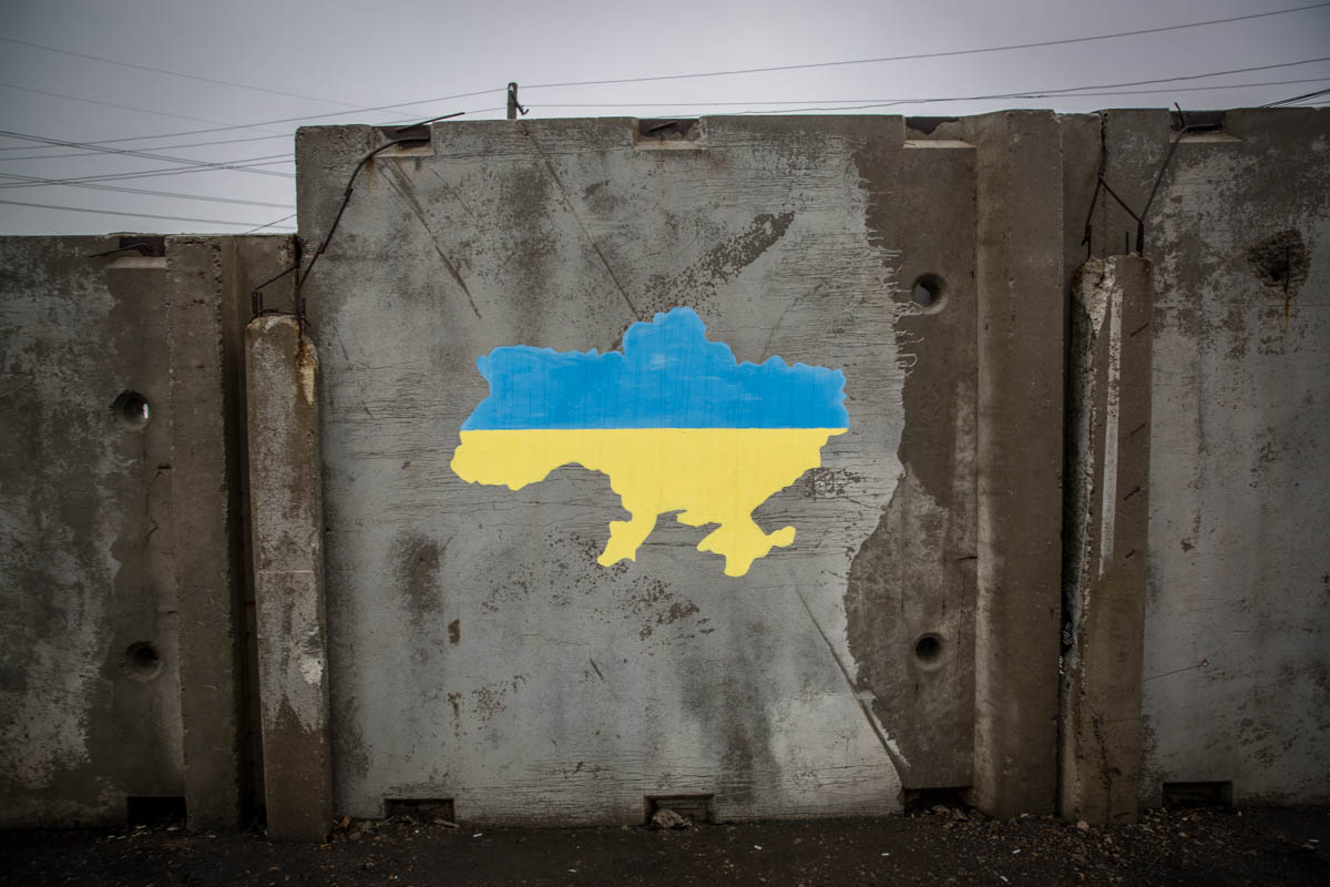 The map of Ukraine before 2014 painted on a separation wall at the checkpoint between government-controlled and non-government-controlled areas in Stanytsia Luhanska in eastern Ukraine. [Ingebjorg Karstad/Norwegian Refugee Council]