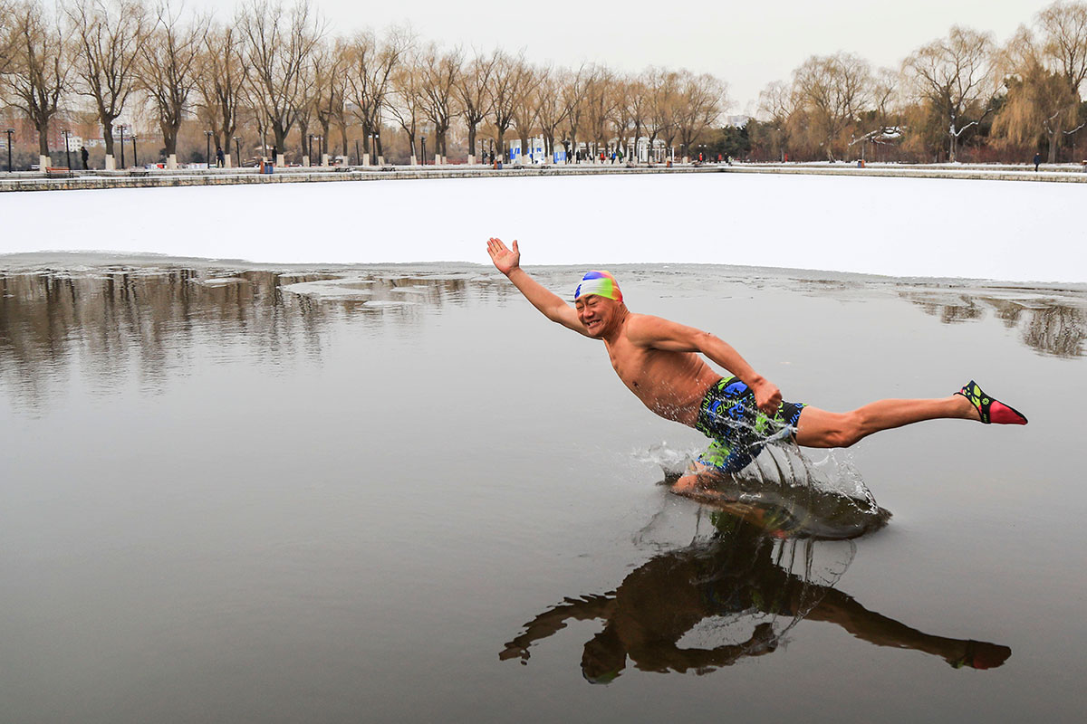 A winter swimmer braves the freezing waters in Beijing Park where air temperatures were as low as -10 Celsius. [VCG/Getty Images]