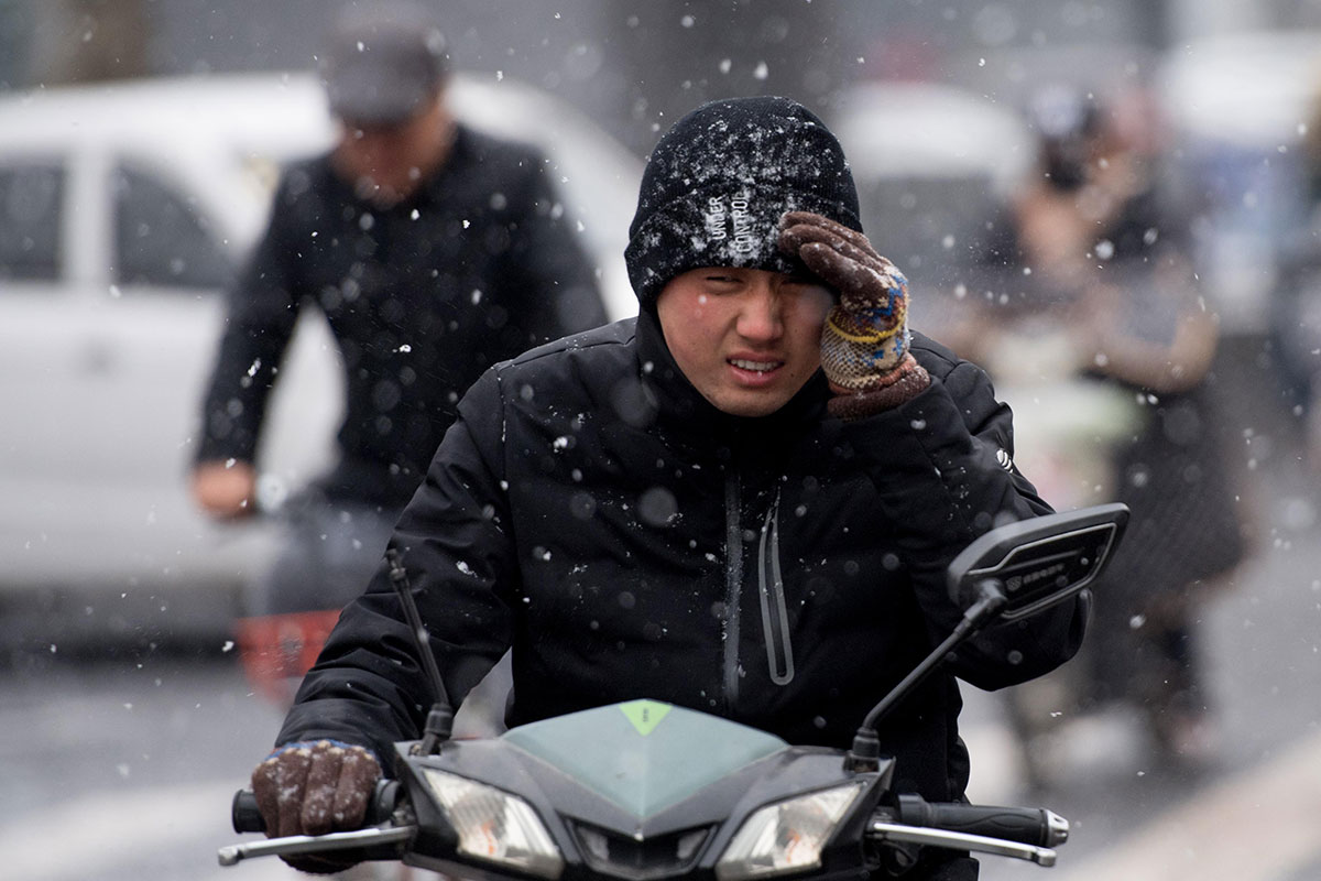 Residents of Taiyuan, China, brave the extreme cold this week. The National Meteorological Center continues to warn of below-average temperatures for the next several days. [Wei Liang/Getty Images]